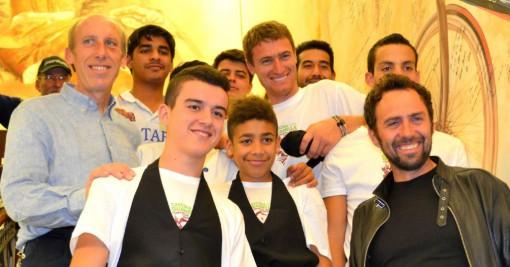 Educatori e ospiti di Casa don Guanella con Simoni accanto al murales dei campioni.
